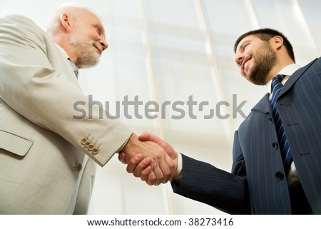Two businessmen shaking hands in front of a modern office centre