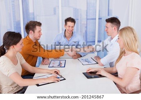 Two businessmen shaking hands in front of colleagues during conference meeting