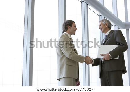 Two businessmen shaking hands in front of large glass windows, with one holding his laptop