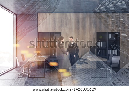 Two businessmen shaking hands in modern open space office with gray walls, wooden bookcases and rows of computer desks. Toned image double exposure #1426095629