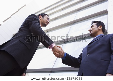 Two businessmen shaking hands outside modern office building