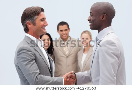 Two businessmen shaking hands with his colleagues in the background