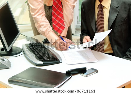 Two businessmen signing contracts at office desk