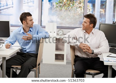 Two businessmen sitting at desk in office, looking at each other talking.