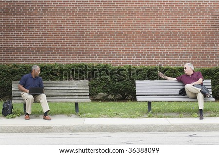 Two businessmen sitting on benches and waiting for a bus - stock photo