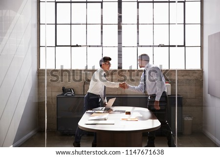 Two businessmen stand shaking hands in an office, side view