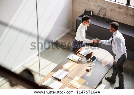 Two businessmen stand shaking hands in office, elevated view