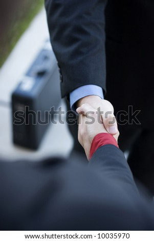 two businessmen standing across from each other shaking hands