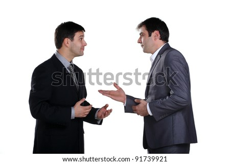 Two businessmen standing and talking with one of them having expression on his face