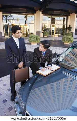Two businessmen standing beside car outside hotel, man signing contract, smiling