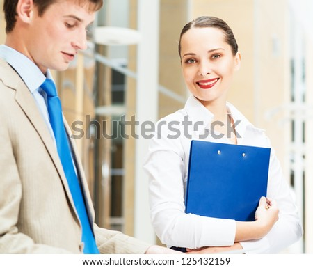 two businessmen standing in the office with documents