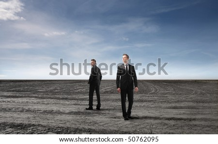 Two businessmen standing on a field