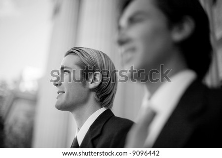 two businessmen standing side by side smiling in front of courthouse