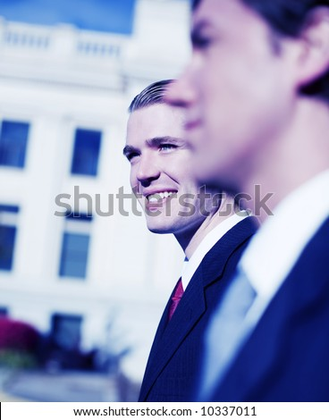 two businessmen standing side by side smiling looking forward