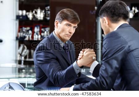 Two businessmen struggle on a forward background