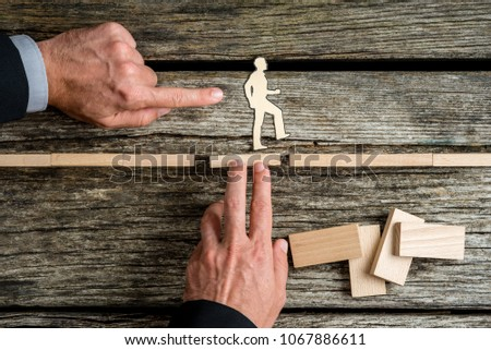 Two businessmen supporting and giving a helping push to silhouette cutouts of a man walking the way to success, conceptual of teamwork. #1067886611