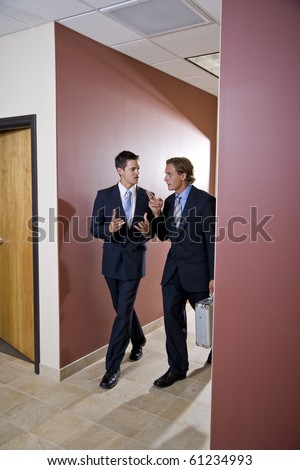 Two businessmen talking and walking down office corridor