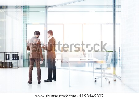 Two businessmen talking in manager office with white walls and floor, gray table with computer on it. Shelves with folders and open plan office in the background. Toned image double exposure #1193145307