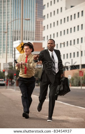 Two businessmen try to outrun each other down the street