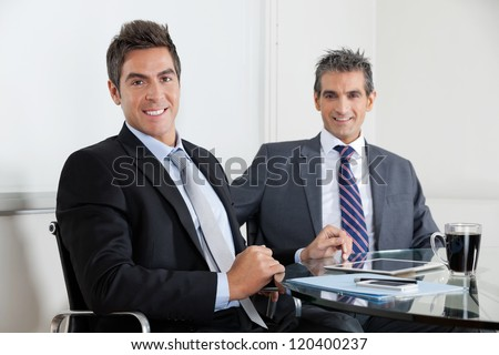 Two businessmen using digital tablet at desk in office