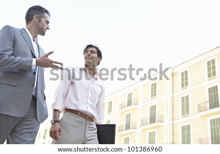 Two businessmen walking in the city and talking.