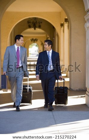 Two businessmen walking side by side in building arcade, luggage in tow, talking, front view