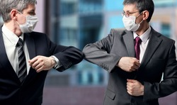 Two businessmen with a medical mask on their faces greet in a new way, striking with their elbows instead of a handshake. Social distance during the coronavirus epidemic