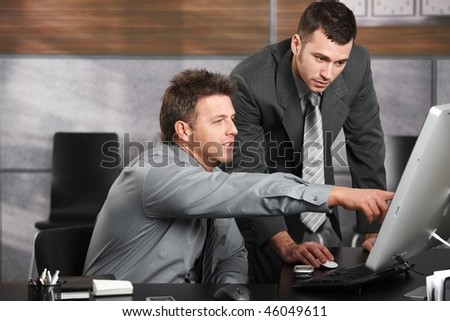 Two businessmen working together with computer at office desk, one of them pointing at screen.