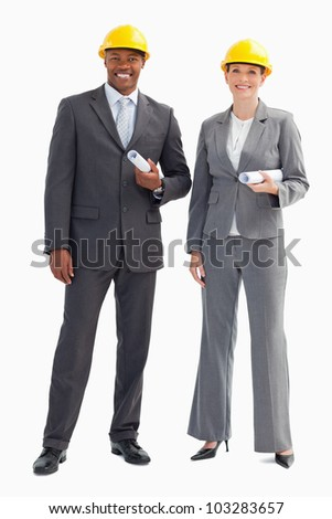 Two businesspeople are wearing hard hats