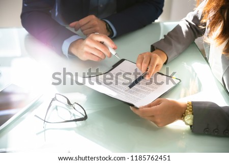 Two Businesspeople Hand Analyzing Document Over Glass Desk #1185762451