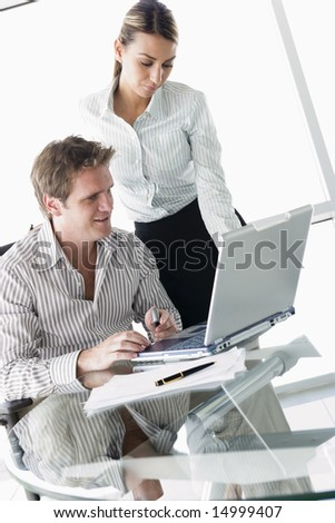 Two businesspeople in boardroom with laptop
