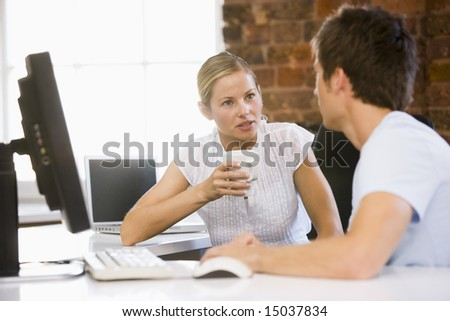Two businesspeople in office drinking coffee and talking