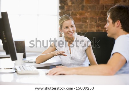 Two businesspeople in office talking and smiling