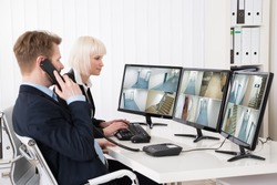 Two Businesspeople Looking At Multiple Camera Footage On Computer