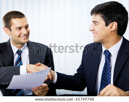 Two businesspeople, or businessman and client, with document handshaking at office - stock photo