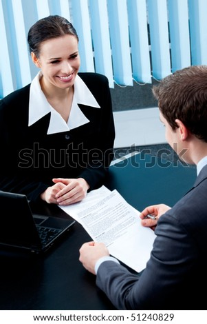 Two businesspeople, or businesswoman and client, with document at office