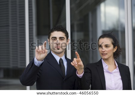 Two Businesspeople pointing on a virtual screen