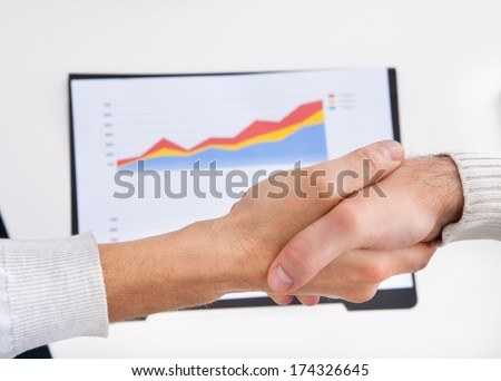 Two Businesspeople Shaking Hand In Front Of Graph