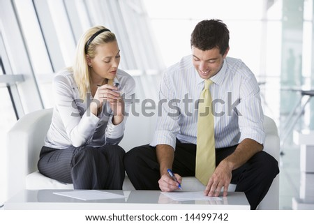 Two businesspeople sitting in office lobby talking and smiling