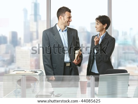 Two businesspeople standing at desk in front of windows in office, talking and smiling.
