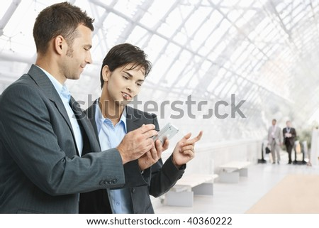 Two businesspeople standing in hallway, looking at mobile phone, smiling.