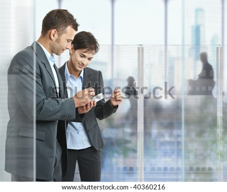 Two businesspeople standing in modern office with glass walls, looking at smart mobile phone.