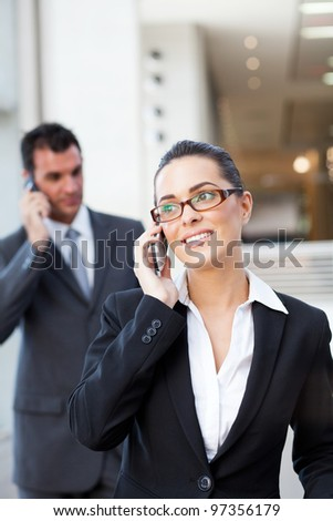 two businesspeople talking on mobile phone