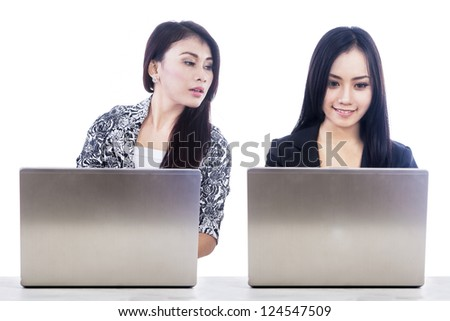 Two businesspeople typing on laptop computer