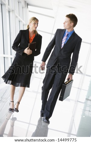 Two businesspeople walking in corridor talking
