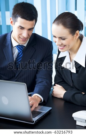 Two businesspeople working with laptop at office