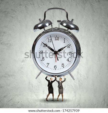 Two businesswoman lifting huge alarm clock above head