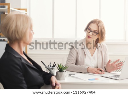 Two businesswoman working. Enterpreneurs discussing new work project sitting in modern office #1116927404