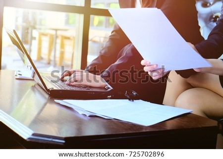 Two businesswoman working together about documents and us laptop , partner discuss plan or idea and opinion meeting, Asian bussiness are discussing their working beside window at coffee shop  #725702896