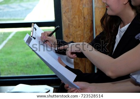 Two businesswoman working together about documents, partner discuss plan or idea and opinion meeting, Asian bussiness are discussing their working on a wood table beside window at coffee shop  #723528514